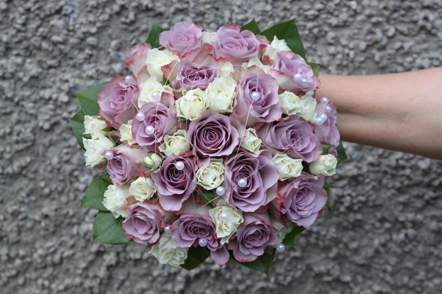 2ad1b4874f10 Brudbukett med lila rosor, vita kvistrosor samt pärlor.